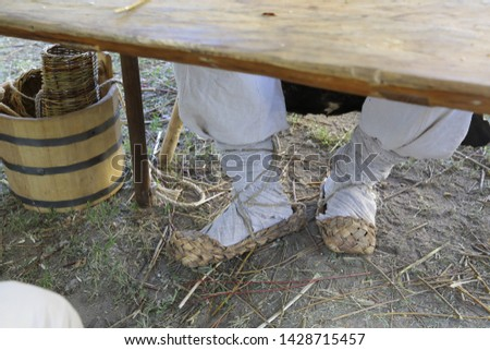 The feet are shod in an old wicker shoes, close-up. Wide wide trousers are tied with footcloths. On the ground is a wooden bucket and village utensils. Russian folk retro style. Handwork. Fashion XIX #1428715457