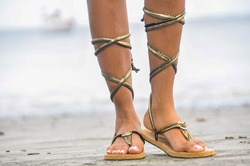 The feet of a caribean girl wearing a pair of golden sandals at the beach