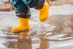 The feet of a child in rubber boots stomp through puddles