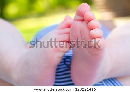 The feet of a newborn baby photographed from below outdoors.