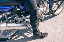 The feet of the man next to the motorcycle close up. Ammunition and special clothing for bikers. Protective devices special shoes knee pads for motorcyclists