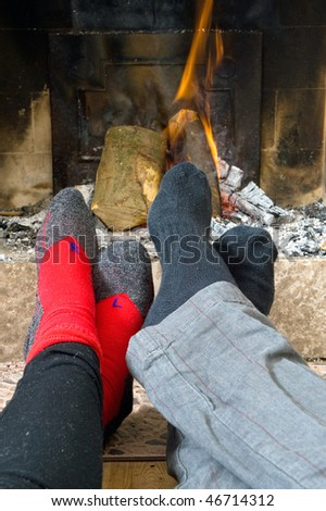 The feet of two hikers warming up by the fire after a long hike on a winter's day