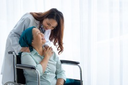 The female doctor was encouraging and inquiring about the symptoms of the elderly patient with a smiling and friendly expression.