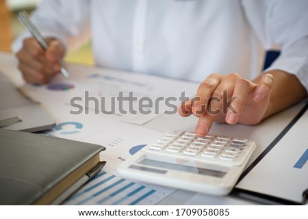The female finance staff is calculating the company's profits from the graph on the home office desk. Concept finance Stockfoto ©
