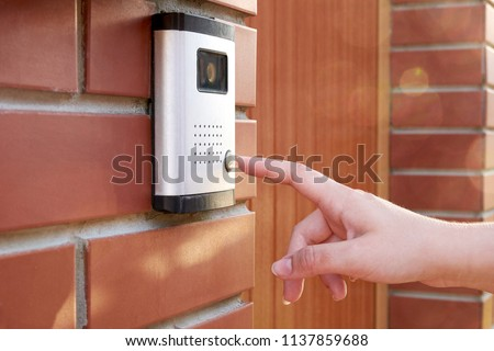 The female hand presses a button doorbell with camera and intercom
