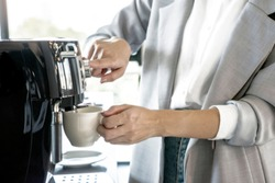 The female in a suit is making coffee from the coffee machine in the morning workplace.