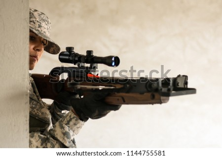 The female soldier in military uniform is holding a crossbow weapon.
