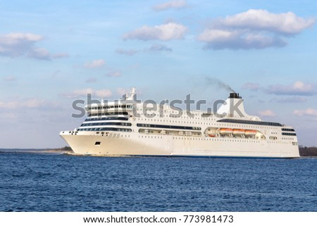 The ferry of white color floats down the river in sunny day against the background of the blue sky and clouds.