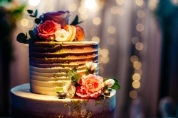 The festive cake is decorated with fresh flowers. Great job confectioner.