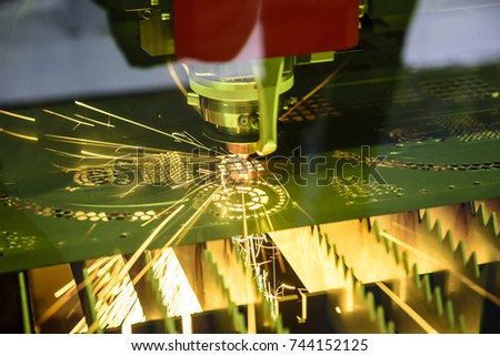 The fiber  laser cutting machine  cutting the sheet metal plate with the sparking light.Hi-technology manufacturing concept. #744152125