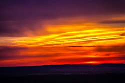 The fiery sky above the silhouette of the horizon of the Russian steppe, bright colorful clouds of red yellow color hide the setting sun. Sunset over Ufa, Bashkortostan, Russia.
