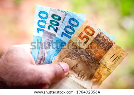 The fifty and one hundred and two hundred reais banknotes is being displayed. The Real is the current money in Brazil