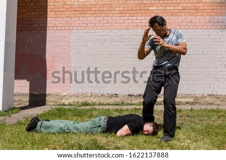 The fight is over. Attacker lies on the ground. Martial arts instructors demonstrate self-defense techniques of Krav Maga