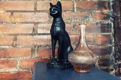The figure of a black cat looking next to the vase.