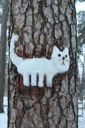 The figure of a cat with snow on a tree in the park. Outdoor entertainment for family Christmas vacation.