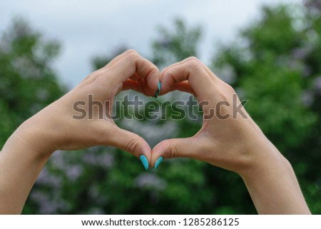 the figure of a heart with your hands in the spring on a background of green trees #1285286125