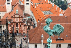 The figure of a rooster on the tower of St. Vitus Cathedral in Prague, the background is blurred