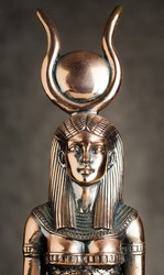 The figure of the Egyptian goddes on a brown corduroy background. Bronze statuette.