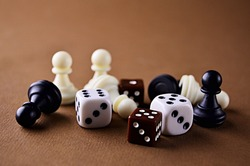 The figures of the board game dice chess backgammon close up on a brown background with a copy space. Play board games. High quality photo