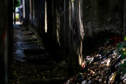 The filthy and dark narrow alley is filled with trash