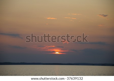 The final stage of a cloudy sunset above the huge lake in Karelia region. The picture is colorful and relaxing.