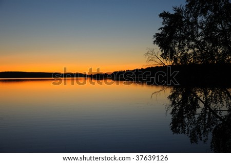 The final stage of a sunset above the huge lake in Karelia region. The picture is colorful and relaxing.