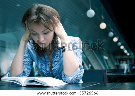 The fine young girl attentively reads the interesting book