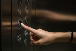 The finger is the push button of the elevator.