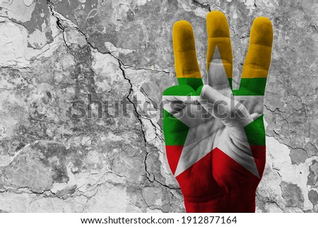 The 3-finger raised as a protest sign with a painted flag of Myanmar. Concept of the people protesting violence, injustice, and dictatorship. Fight for democracy. 3D Illustration, 3D rendering Photo stock ©