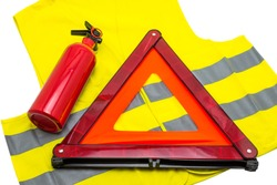 The fire extinguisher and reflective warning triangle lie on the reflective vest, isolated on a white background with a clipping path.