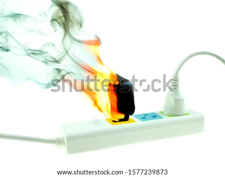 The fire is burning adapter charger plug receptacle on white background, Electric short circuit failure resulting #1577239873