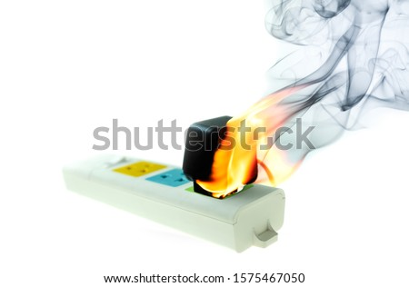 The fire is burning adapter plug receptacle at white background, Electric short circuit failure resulting #1575467050