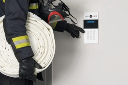 the firefighter carries equipment for extinguishing fires, communicates via intercom with the building security