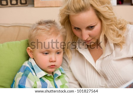 The first book, portrait of attractive mom and son reading a book together.