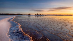 The first ice  off the coast on the water in Lake Ladoga at dawn with fresh snow in winter at sunset