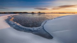 The first ice on the water in Lake Ladoga at dawn with fresh snow in winter