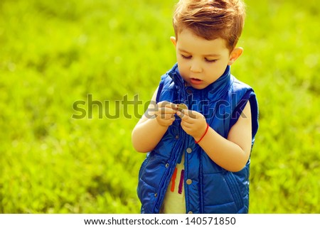 The first investment concept. Portrait of a stylish baby boy with ginger (red) hair holding coins in the park. Hipster style. Sunny weather. Copy-space. Outdoor shot
