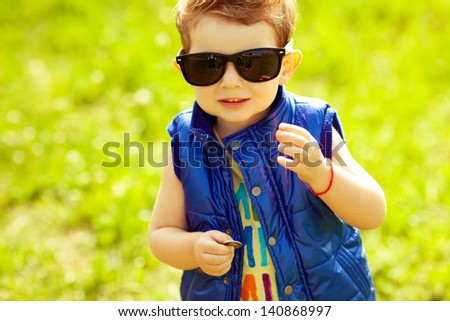 The first investment concept. Portrait of a stylish happy baby boy with ginger (red) hair holding coins in the park. Hipster style. Sunny weather. Copy-space. Outdoor shot