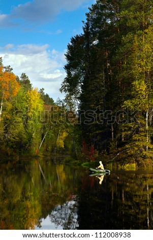The fisher in boat is on the forest lake in autumn. There's a very quietly here.  Water mirror on lake is reflect bright color of leaves on the trees.