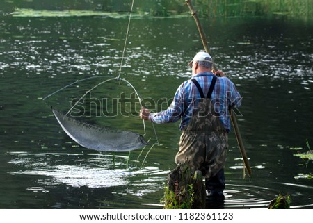 The fisherman catches a small fish for bait. #1182361123