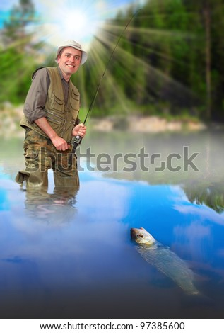 The fisherman catching a fish on a wild river in rural landscape.
