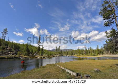 The fisherman in a red waistcoat fishes in shallow northern river - stock photo