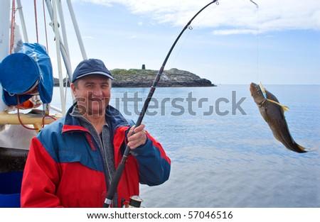 The fisherman on the boat near the island Skrova
