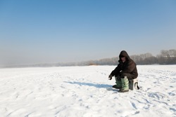 The fisherman on winter fishing in frosty day