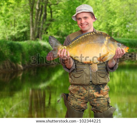 The fisherman with his big carp at a beautiful river. - stock photo