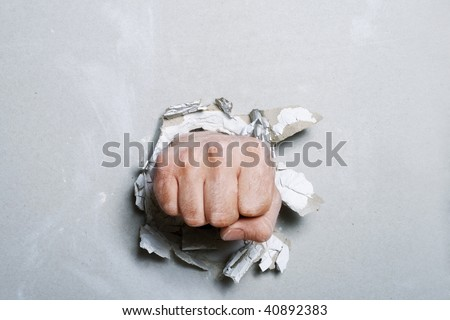 The fist has punched wall, than has created the torn hole
