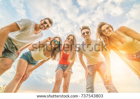 The five happy friends look to the camera on the blue clouds background