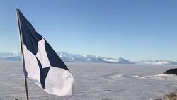 The flag of Antarctic flies above the Ross Ice Shelf near McMurdo Station, Antarctica