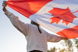 The flag of Canada in the hands of a person. Canadian symbol against the backdrop of a beautiful sunset. Pride and independence