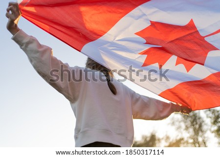 The flag of Canada in the hands of a person. Canadian symbol against the backdrop of a beautiful sunset. Pride and independence Stockfoto ©